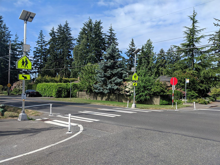 Solar powered flashing beacons are placed on either end of a crosswalk going across a residential street.