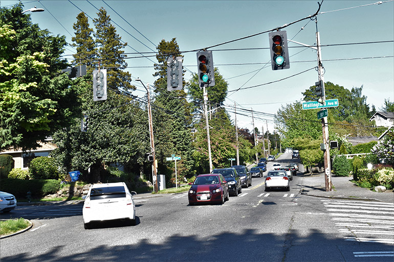 Cars move at the green light and wait at the red light at the intersection of Wallingford Ave N and N 80th St.