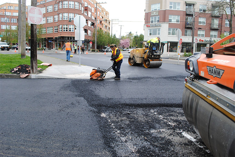 Construction workers roll over fresh asphalt and one worker tamps down asphalt with handheld machine to detail around curbs.