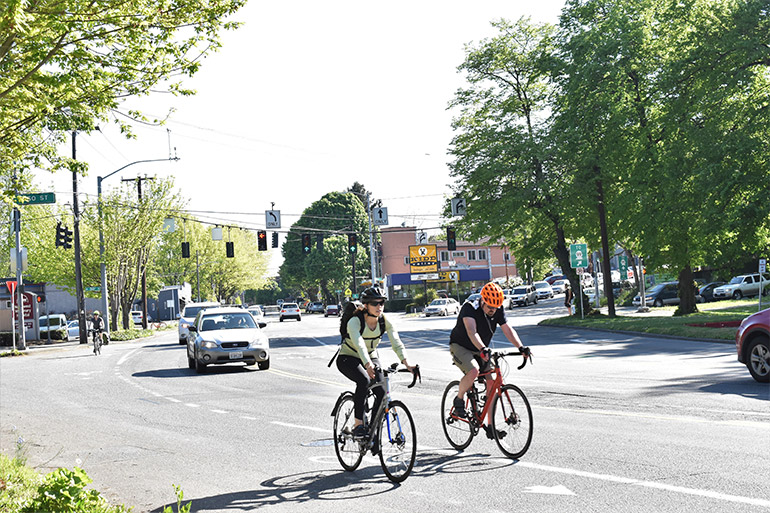 Two bikers riding next to each other along the bike lane near the intersection of Green Lake Way N, N 50th St, and Stone Way N.