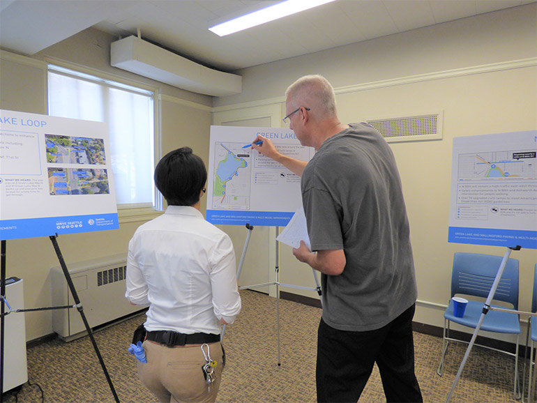 A member of the project team listens while a member of the public points to a display board and asks a question about the project design.